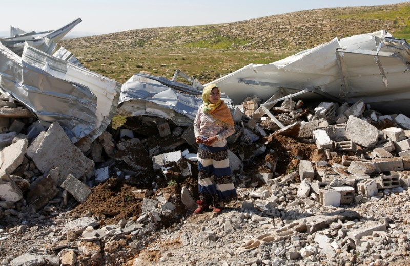 A Palestinian woman stands in front of her demolished house that army told them they didn't obtain a construction license, near Yatta in the Israeli-occupied West Bank March 20, 2019. REUTERS/Mussa Qawasma