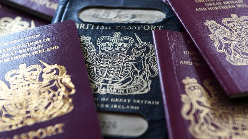 Post-Brexit UK passports are expected to be blue, but burgundy ones without the EU label are being issued. [Andy Rain/EPA-EFE]