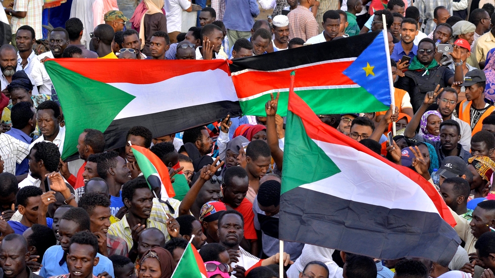 Sudanese demonstrators display their national flag and the national flag of South Sudan, as they attended a sit-in protest outside the defence ministry in Khartoum [Reuters]