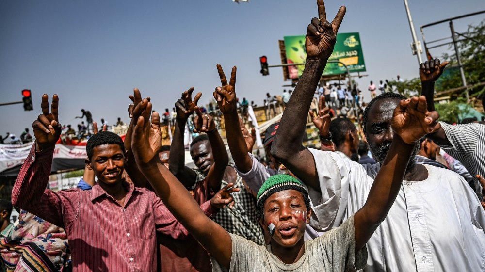 Sudanese protesters chant slogans and flash victory signs as they continue to protest outside the army complex in Khartoum [Ozan Kose/AFP]