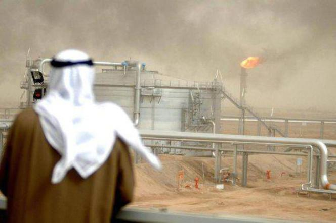 An employee of the Kuwait Oil Company (KOC) looks at an oil refinery. (File Photo: AFP)