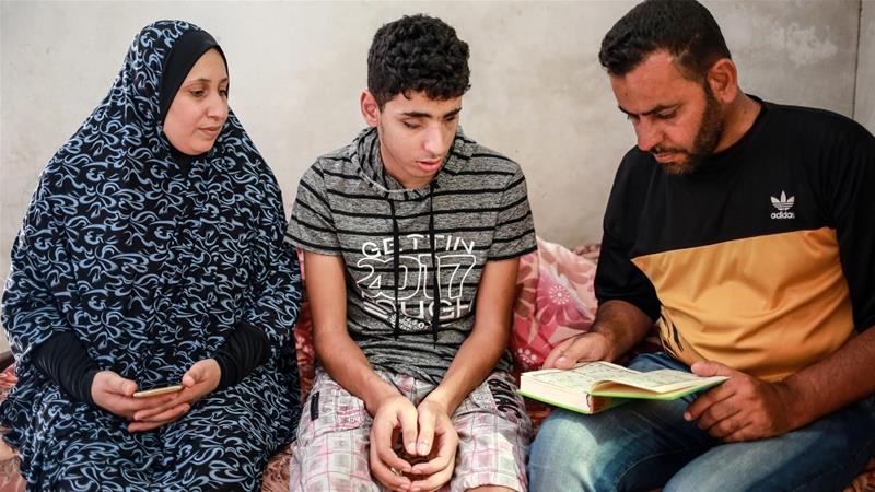 Saleh Ashour, 16, who was blinded by an Israeli bullet last year, sits between his parents at their home in the Gaza Strip [Hosam Salem/Al Jazeera]