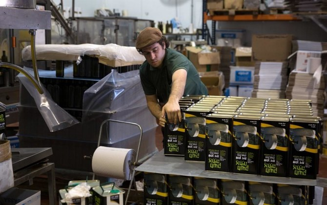 An Israeli settler prepares olive oil containers at the Achia Olive press factory in the Jewish settlement of Shilo in the occupied West Bank. (File/AFP)
