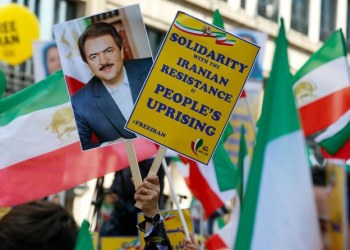 People wave Iranian national flags and hold signs as they take part in a march organised for a free Iran and protesting against the Iranian regime, on June 15, 2019 in Brussels. (AFP)