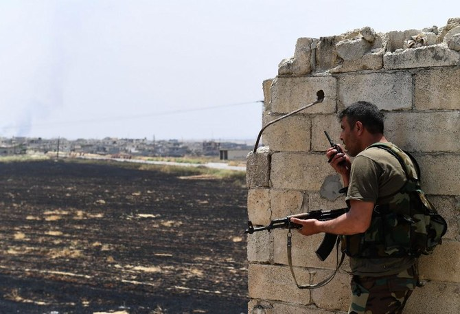 A fighters with the Syrian regime forces holds a position in Syria's Hama governorate during clashes with militants earlier on June 8, 2019. (AFP)