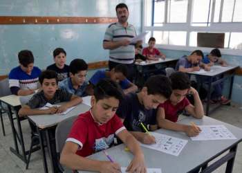 In this Sunday, May 26, 2019 photo, a teacher supervises while Palestinian school children attend a final exam during the last day of the school year. (AP)