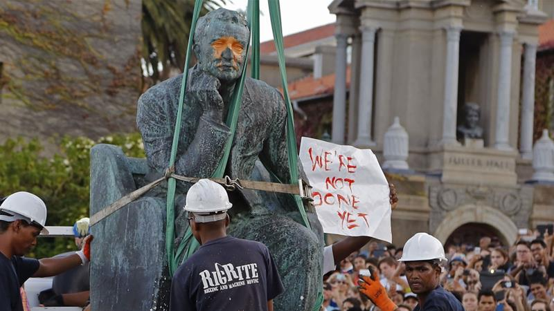 Students surround the bronze statue of British colonialist Cecil Rhodes, as it is removed from the campus of Cape Town University, South Africa on April 9, 2015 [File:AP/Schalk van Zuydam]