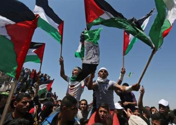 Demonstrators hold Palestinian flags during a protest marking the 71st anniversary of the Nakba in the southern Gaza Strip on May 15, 2019 [Reuters/Ibraheem Abu Mustafa]
