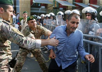 Lebanese army soldiers hold a veteran during a protest against any cuts to their benefits in the state budget, at downtown Beirut, Lebanon July 19, 2019. (Reuters)