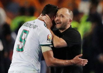 Algeria's Baghdad Bounedjah is embraced by coach Djamel Belmadi after he is substituted off, as his goal was enough to secure Algeria a second Africa Cup of Nations win. (Reuters)