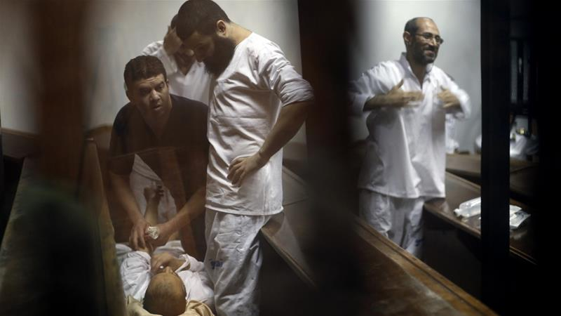 Prisoners appear in a soundproof glass cage inside a makeshift courtroom in Cairo [Roger Anis/AP]