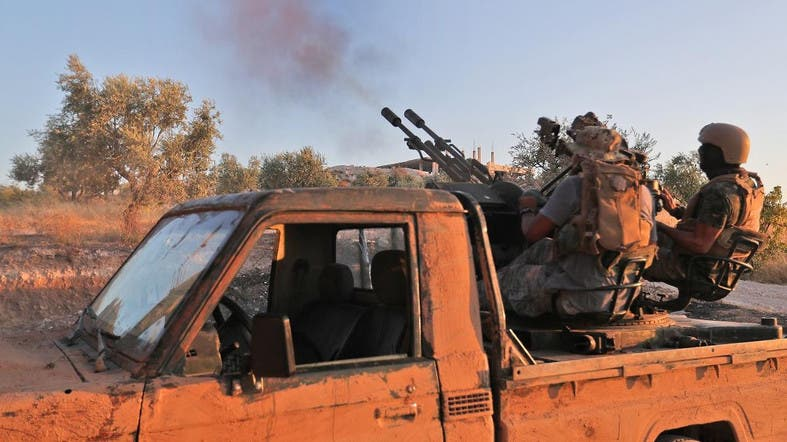Fighters from the former al-Qaeda Syrian affiliate Hayat Tahrir al-Sham (HTS) fire an anti-aircraft gun mounted on a pickup truck in Syria's southern Idlib province on August 7, 2019. (AFP)