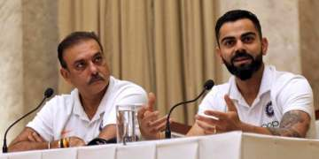 Indian cricket team coach Ravi Shastri (left), looks on as captain Virat Kohli addresses a press conference ahead of the team's departure to West Indies in Mumbai, India, on July 29, 2019. (AP)