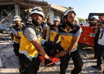 Members of the Syrian Civil Defence carry away a body on a stretcher following a reported government air strike in the village of Benin, about 30 kilometers south of Idlib in northwestern Syria. (AFP)