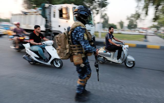 Men ride motorbikes past a member of Iraqi federal police in a street in Baghdad, Iraq October 7, 2019. REUTERS/Wissm al-Okili