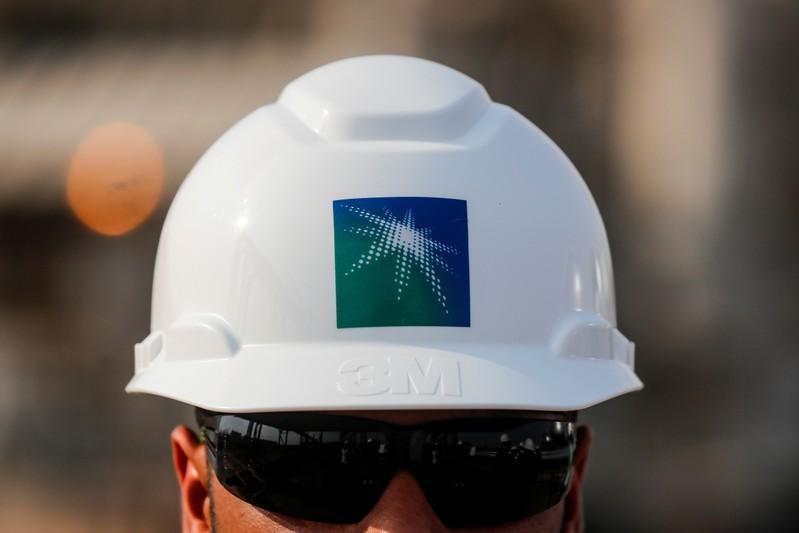 FILE PHOTO: An employee in a branded helmet is pictured at Saudi Aramco oil facility in Abqaiq, Saudi Arabia October 12, 2019. REUTERS/Maxim Shemetov/File Photo