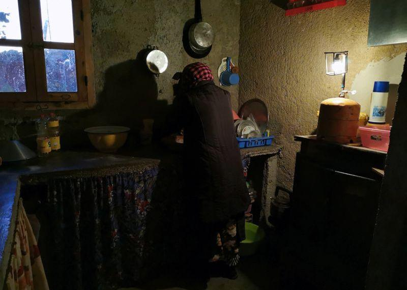 FILE PHOTO: Mohammed Akki's wife works in the kitchen of their home that has no electricity and is lit by a gas lamp in the community of Ait Hammou Ouhmad on the edge of Azrou in Morocco, November 6, 2019. REUTERS/Abdelhak Balhaki