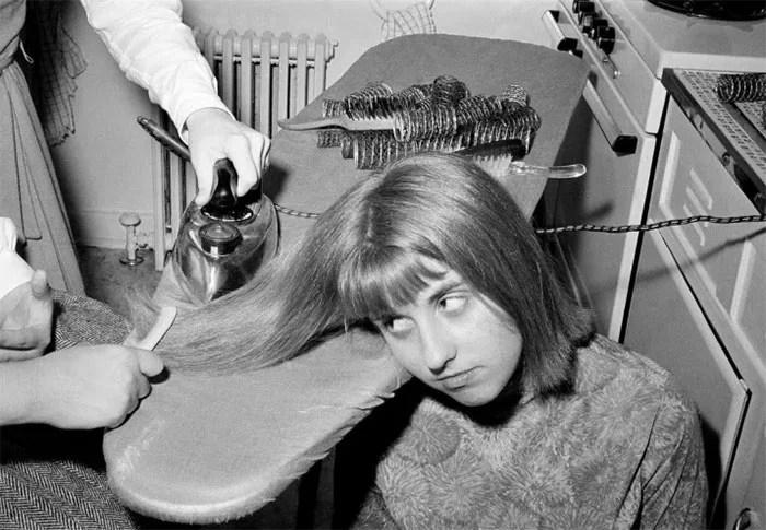 mulher passando ferro no cabelo - Coisas estranhas do passado a que as mulheres se sujeitaram em nome da beleza (Não se assuste!)