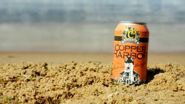 Copper Harbor Ale sitting in the sand on the beach.