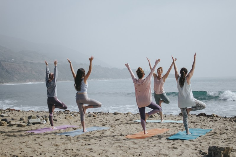 Group of people taking a yoga class on the beach