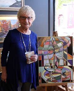 Woman standing next to a painting.