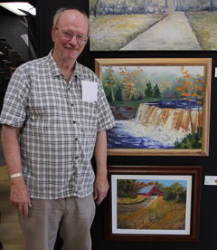 man standing next to oil painting of a barn