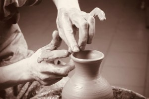 Two hands making pottery