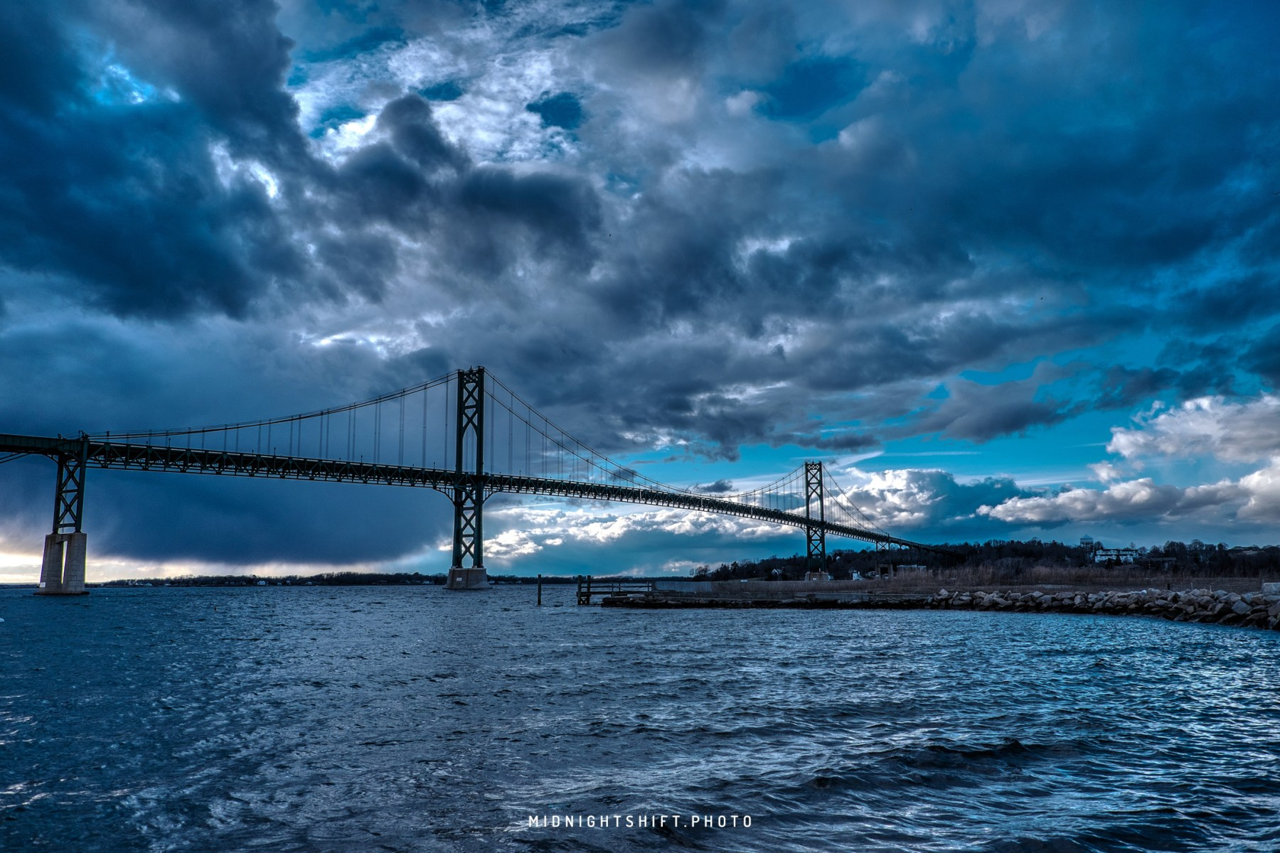 A storm breaks over the Mt Hope Bridge inbetween bristol and portsmouth Rhode Island