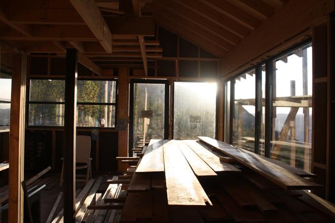 Bilde av stua. Mye vinduer - mye plank. Forhåpentligvis vil dette bli byttet ut med en sofa og et bord når hytta begynner å nærme seg ferdig. En plankehaug i stua er upraktisk.