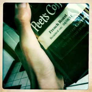 holding a new bag of Peets coffee