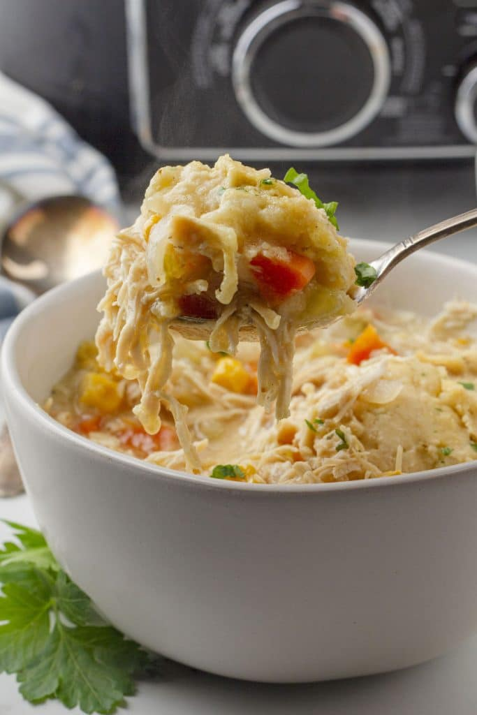A spoonful of crockpot chicken and dumplings held above a full bowl of this delicious comfort food.
