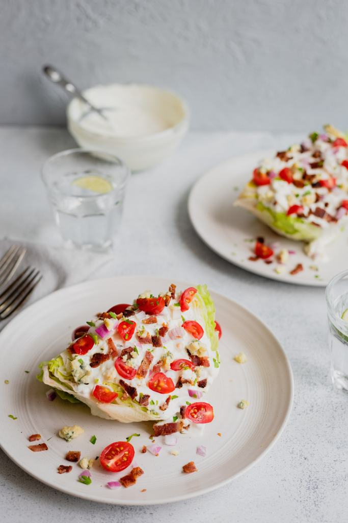 Two pieces of iceberg wedge salad sit on white plates on a white background with grey napkins. There are glasses of sparkling water on the side.