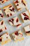 Rhubarb Cheesecake Square sit on a piece of parchment paper