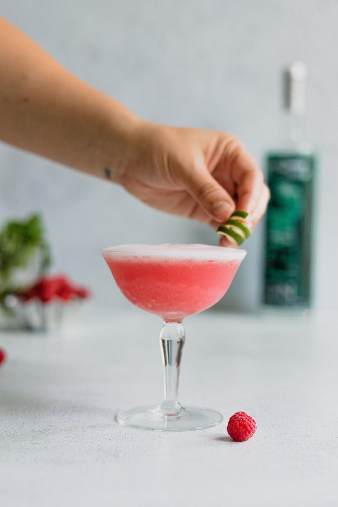 A hand reaches out to garnish a raspberry gin fizz with a lime twist. A raspberry sits behind the vintage glass on a gray background.