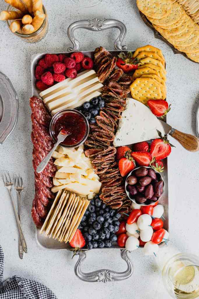 A cheese board filled with red, white, and blue foods to celebrate Fourth of July on a speckled gray background.