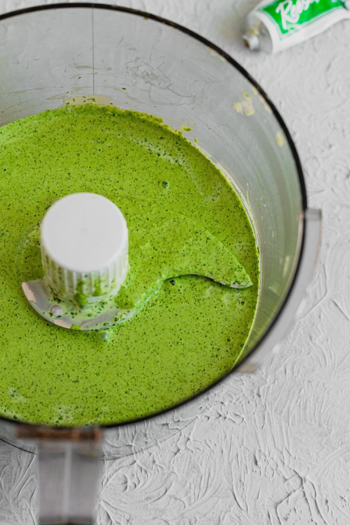 Smooth and blended Green Goddess Salad Dressing in the bowl of a food processor on a grey background.
