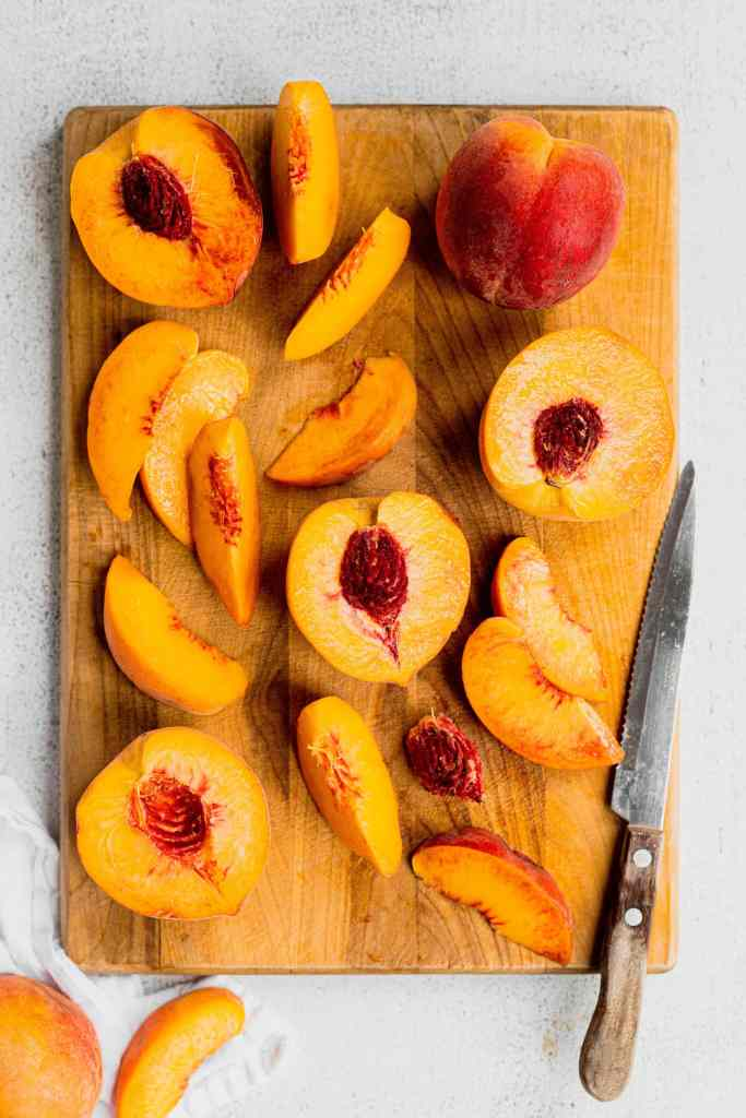Fresh peaches that are whole, halved, and sliced sit on a brown cutting board. A wood handled knife sits on the right hand side of the board.