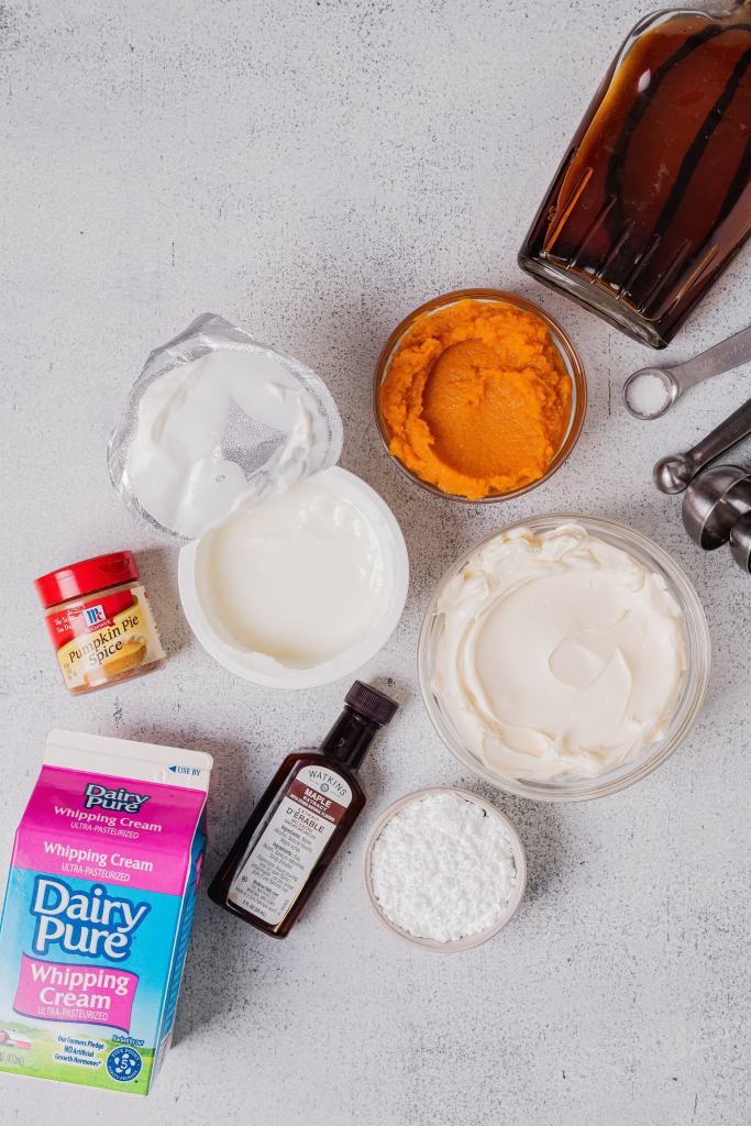 All of the ingredients for the pumpkin pie dip recipe are laid on a white speckled backdrop.