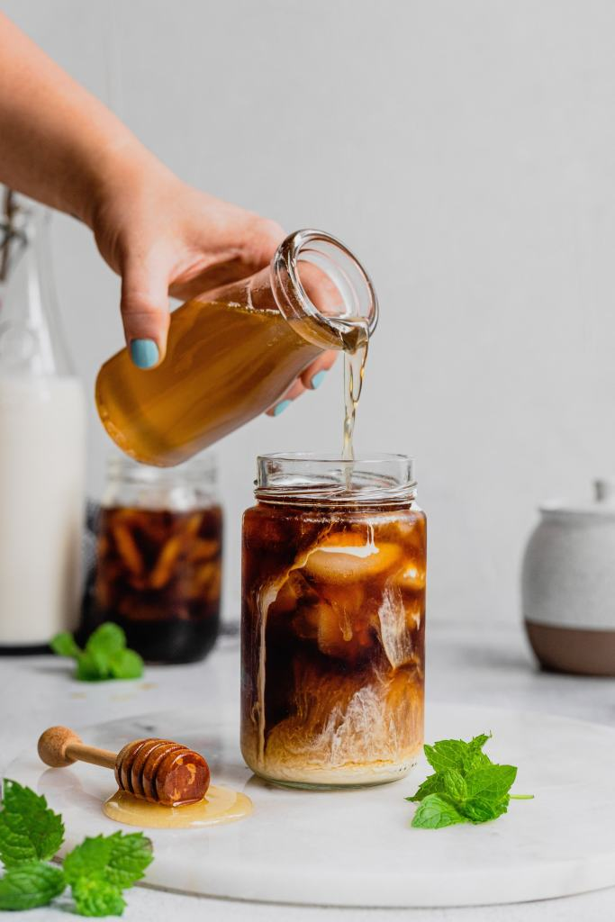 A woman's hand pours a splash of honey mint simple syrup into a glass of cold brew coffee with cream. There is a honey dipper and sprigs of mint on the round marble board the cup is set on.