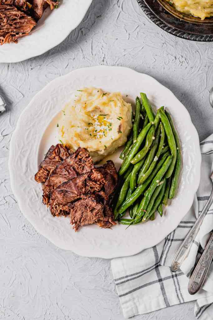An overhead shot of a white plate filled with beer braised beef roast, buttery mashed potatoes, and sautéed green beans. There is a white and blue checkered napkin next to the plate.
