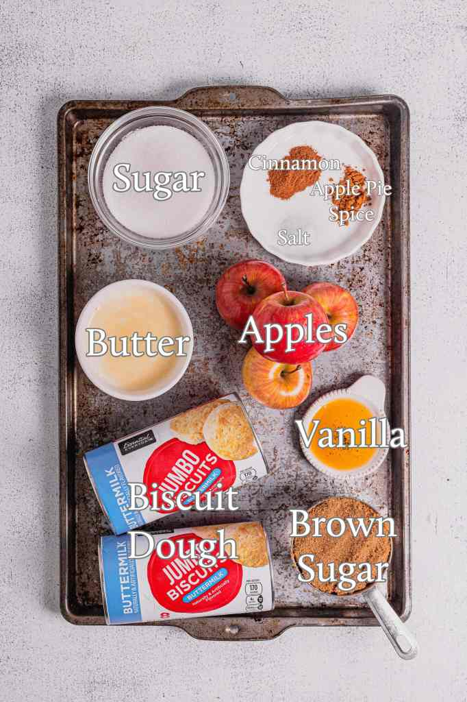 A baking tray filling with the ingredients for this apple cinnamon monkey bread recipe. They are: sugar, butter, biscuit dough, brown sugar, vanilla, apples, salt, apple pie spice, and cinnamon.
