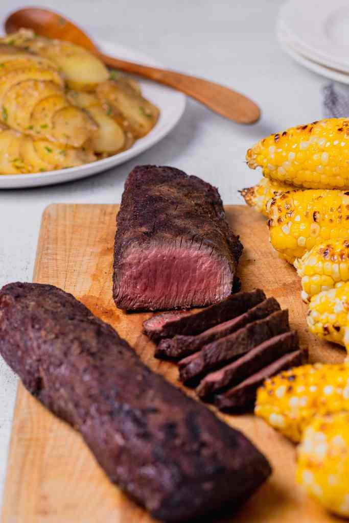 A straight on shot of a grilled venison backstrap that has been cut to expose the center. The venison rests on a wooden cutting board with grilled corn.