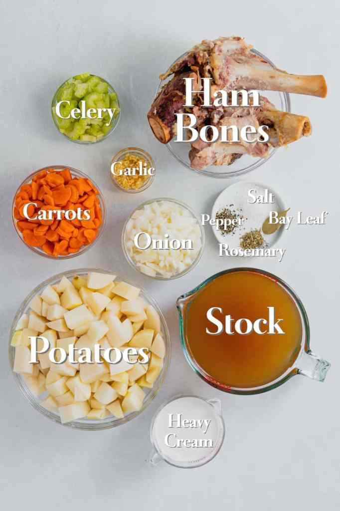 All the ingredients for slow cooker potato and ham soup are in glass bowls and measuring cups on a white background. Every ingredient is labeled.