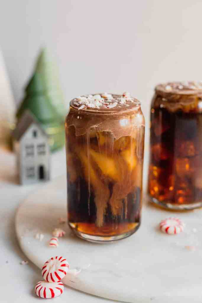 A glass is filled with peppermint mocha cold foam cold brew and topped with crushed peppermint candies. It sits on a white marble board with another glass of coffee behind it and Christmas decorations in the background.