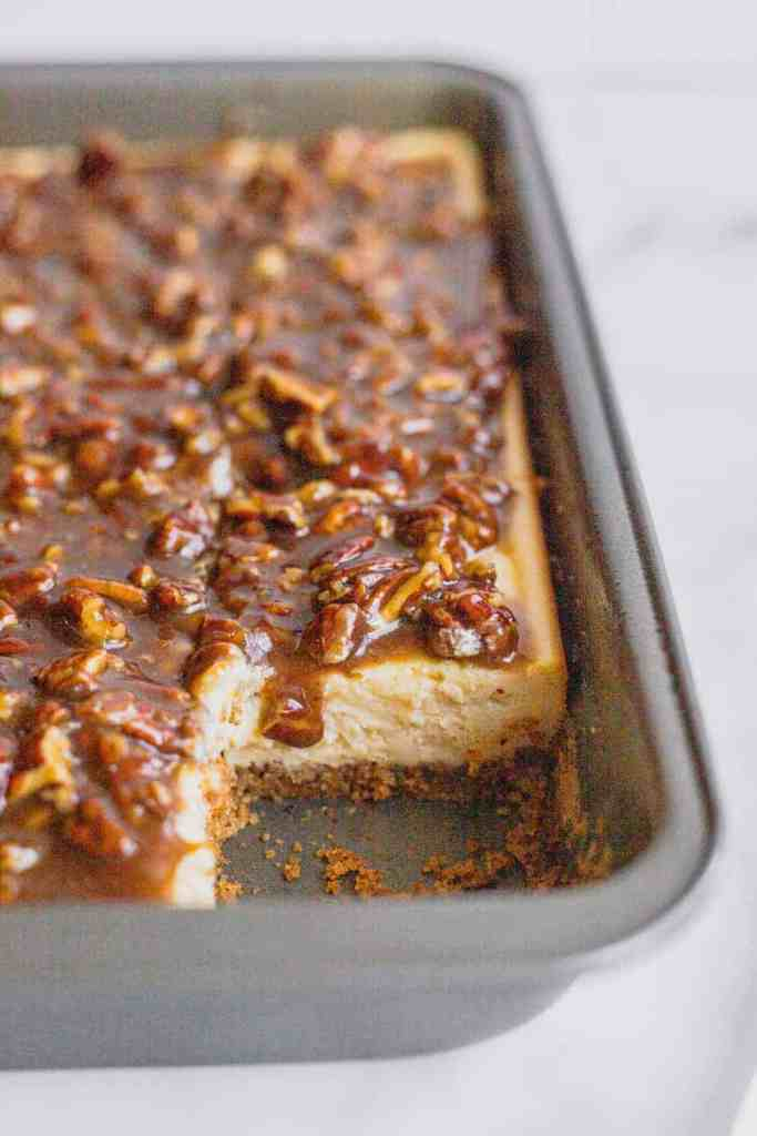 A silver baking tray filled with maple pecan pie cheesecake bars. A corner piece of the bars is removed to show the layers in the bars. A drip of pecan pie filling drips down the cheesecake.