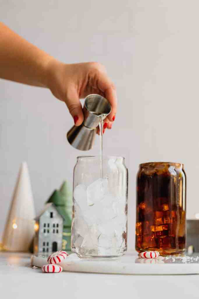 Peppermint Simple Syrup is added to a glass filled with ice.
