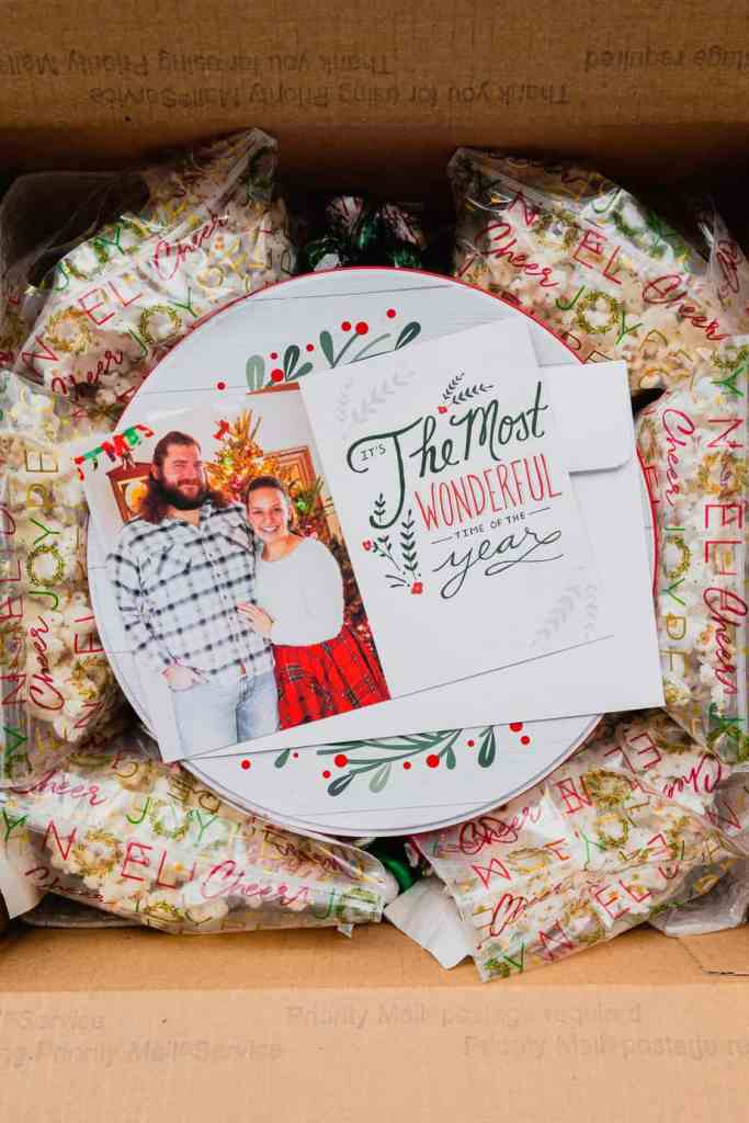 A holiday card sits on a tin of cookies that will be sent in the mail. There are bags of popcorn around the tin in a box to protect it from getting crushed.