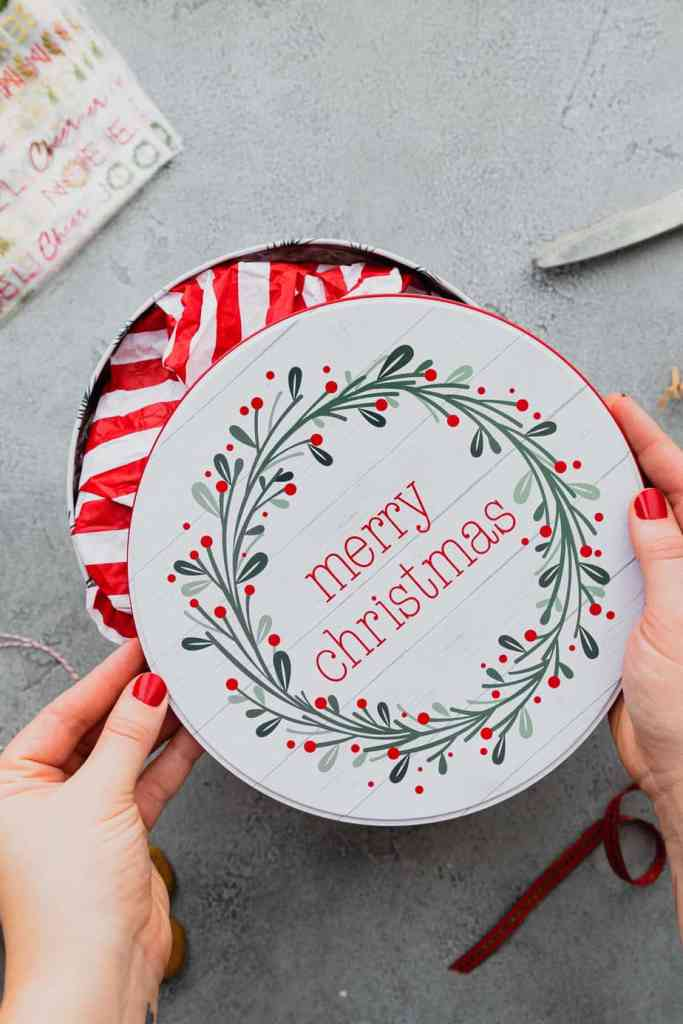 "A pair of hands puts the lid on a tin of Christmas cookies that are ready to be mailed. The tin says ""Merry Christmas"" in red with a green wreath around it."
