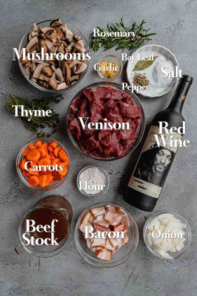 All the ingredients for red wine venison stew are laid out on a grey backdrop in various glass bowls and measuring cups.