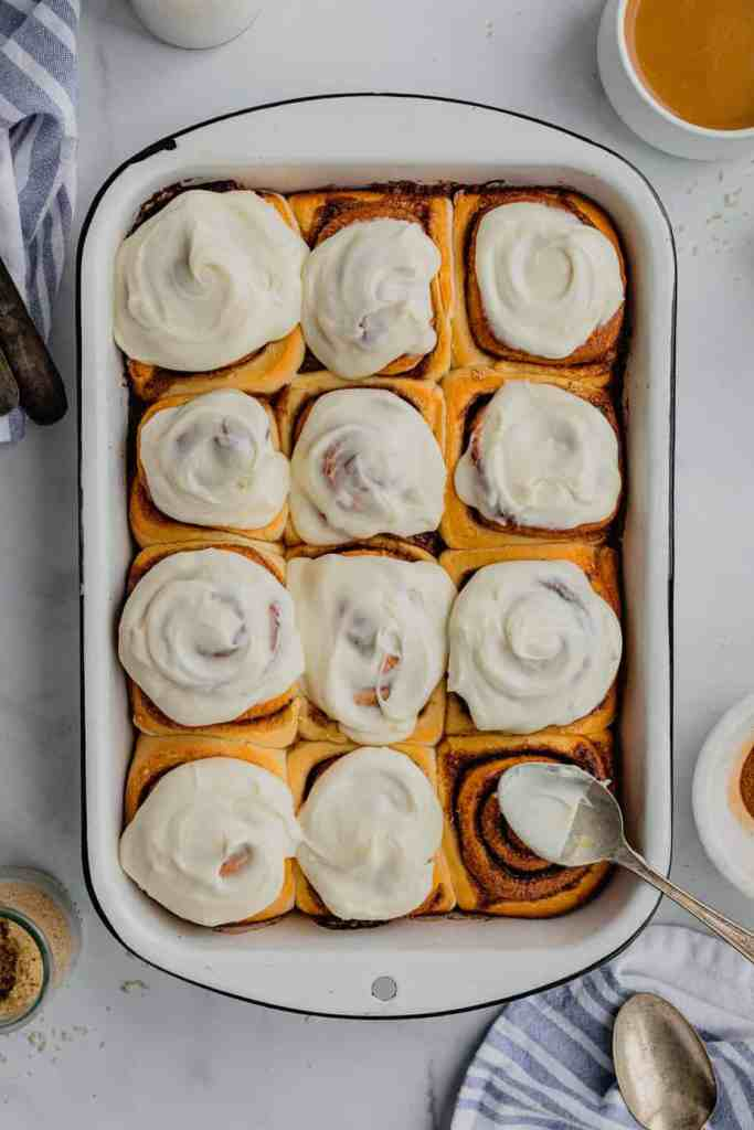 A white enamel dish filled with overnight cinnamon rolls recipe covered in cream cheese frosting.